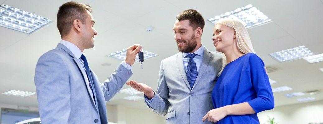 A stock photo of a young couple taking keys from a sales person.