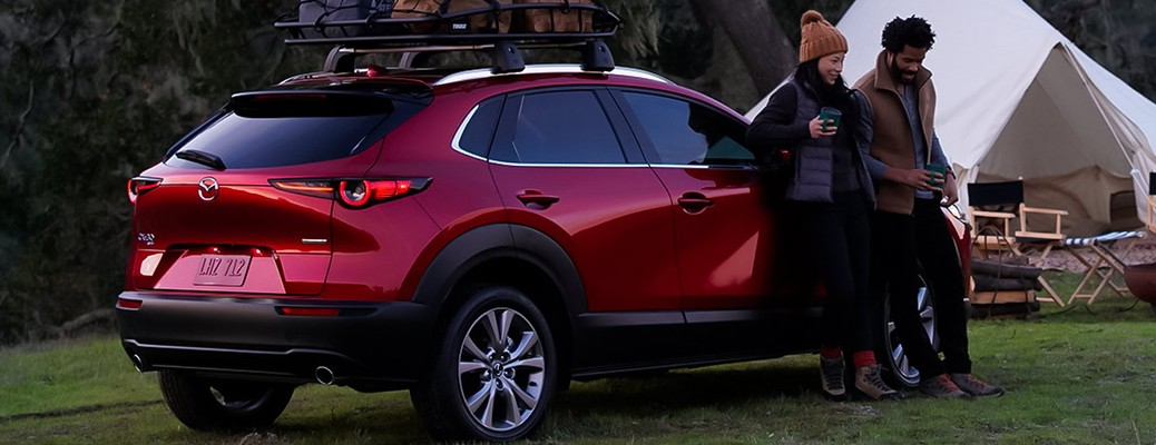 Two people standing next to a Mazda CX-30