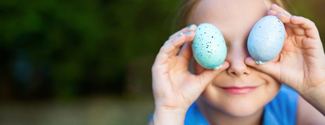 Little boy holding Easter eggs over his eyes