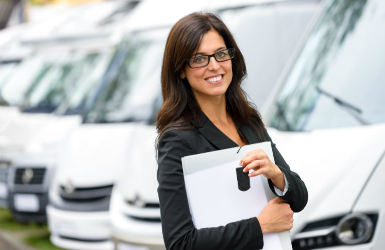 woman holding keys and paperwork smiling in front of cars