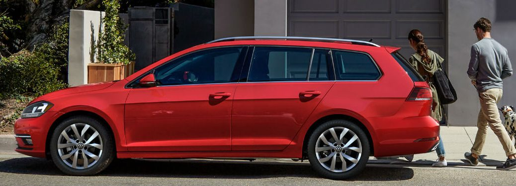 A couple and their dog enters a 2018 Volkswagen Golf SportWagen