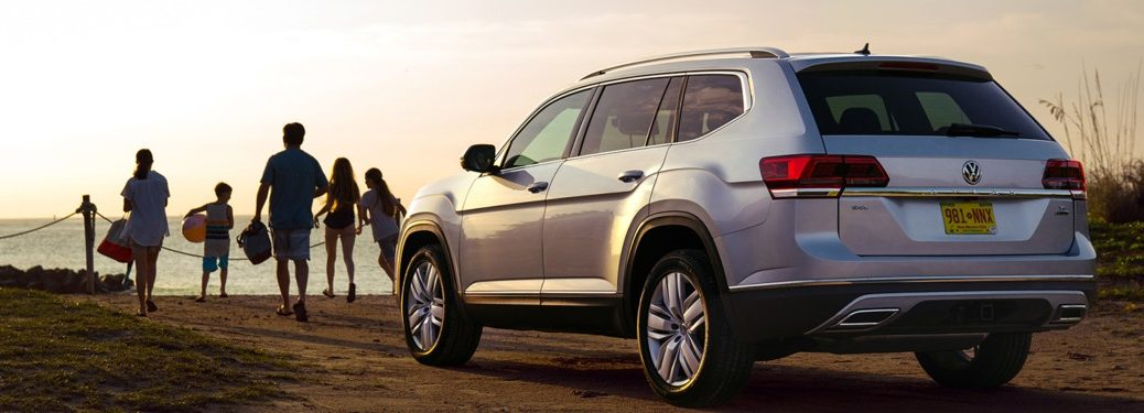 2019 Volkswagen Atlas parked on the beach with a family nearby