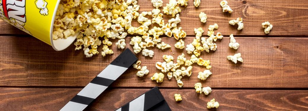 Close-up on a clapperboard and spilled popcorn on a wooden background