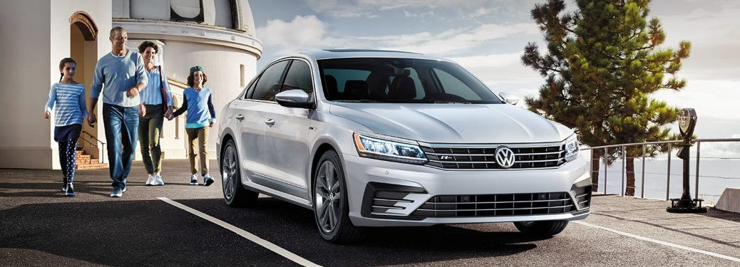 A family walks towards a parked 2019 Volkswagen Passat