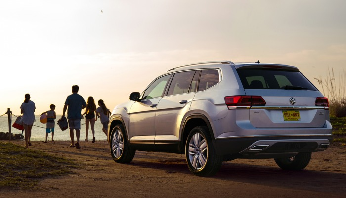 2019 Volkswagen Atlas parked on a beach at sunset with a family nearby