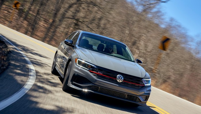 2019 Volkswagen Jetta GLI driving down a curved road in the forest