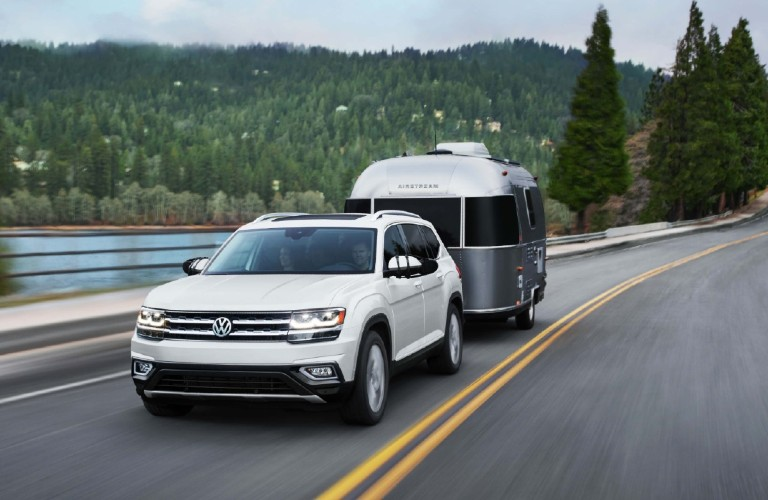 A white 2020 Volkswagen Atlas using an available tow hitch to tow an Airstream travel trailer.