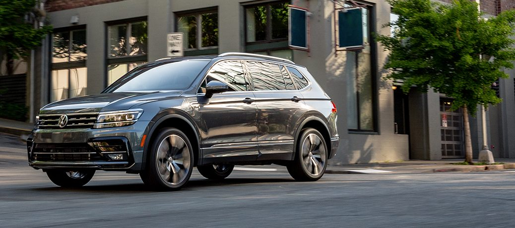 A gray 2020 Volkswagen Tiguan driving in a city intersection.