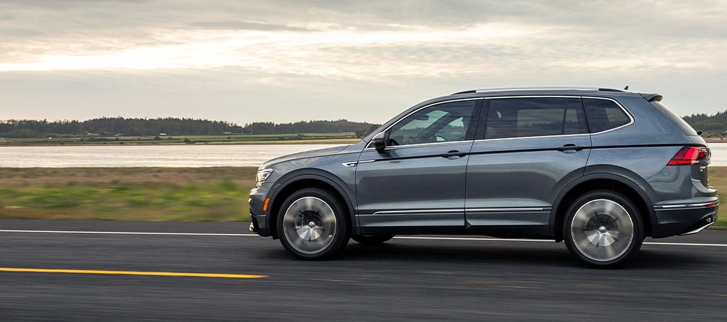A gray 2020 Volkswagen Tiguan driving down an open road with a forecast sky overhead.