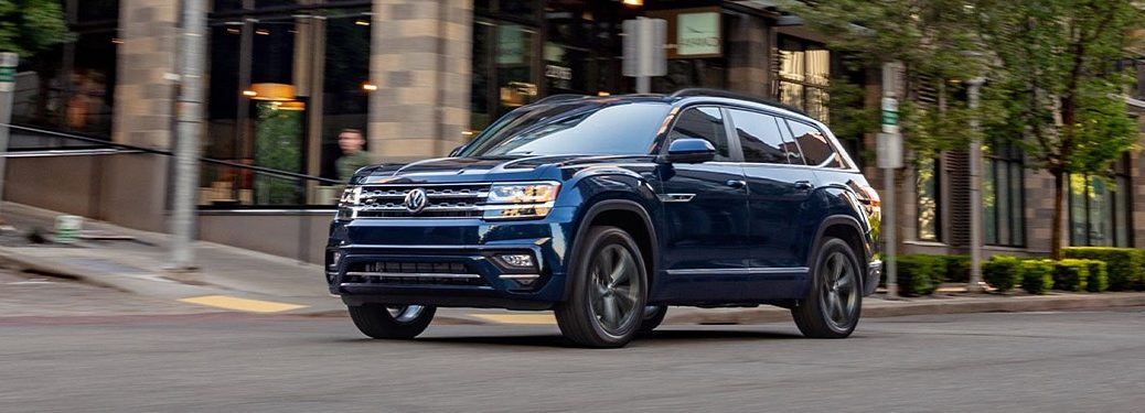 A blue 2020 Volkswagen Atlas driving down a city road.