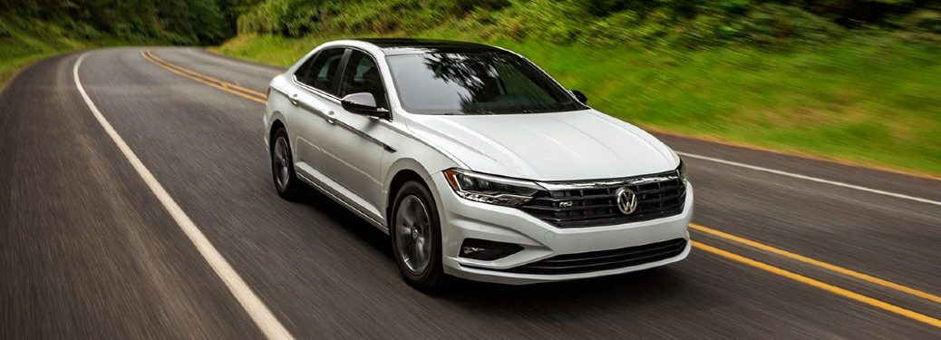 A white 2020 Volkswagen Jetta driving down an open road in a grassy area.