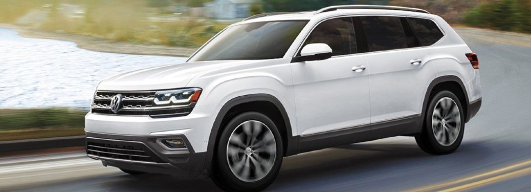 The side and front view of a white 2020 Volkswagen Atlas driving down a country road.