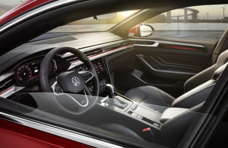 The front seating area inside a red 2021 Volkswagen Arteon.
