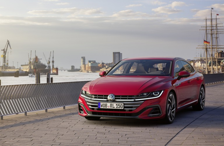 A front image of a red 2021 Volkswagen Arteon next to a dock area.