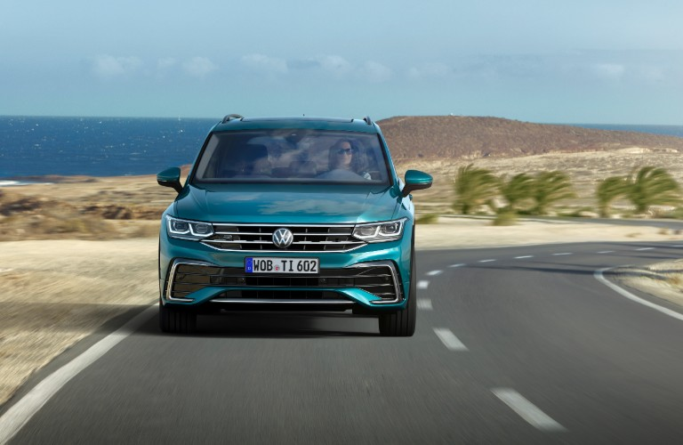 The front side of a teal 2022 Volkswagen Tiguan driving down an open road.