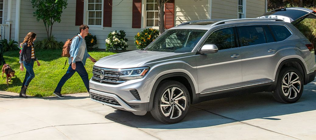 The front and side view of a gray 2021 Volkswagen Atlas parked at a family home.