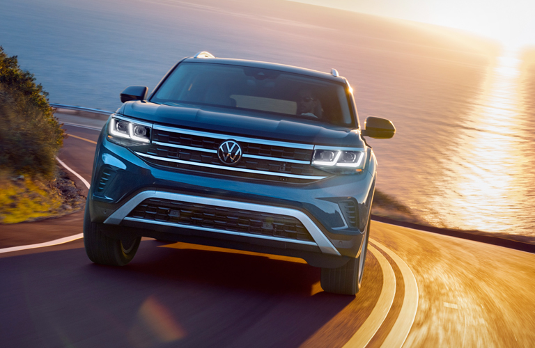The front side of a blue 2021 Volkswagen Atlas driving up a hill during sunset.
