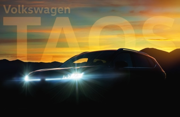 """A shadowed image of the 2021 Volkswagen Taos with the caption """"Volkswagen Taos"""" in the background."""