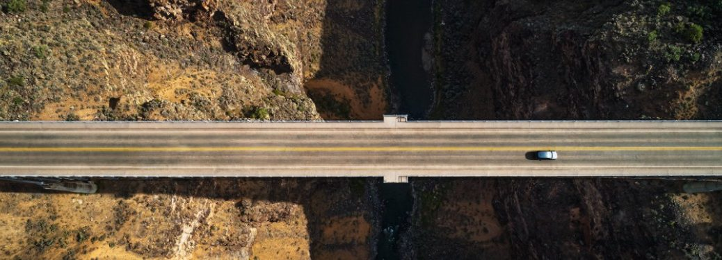 A top-down image of a bridge with a 2021 Volkswagen Taos driving on it.