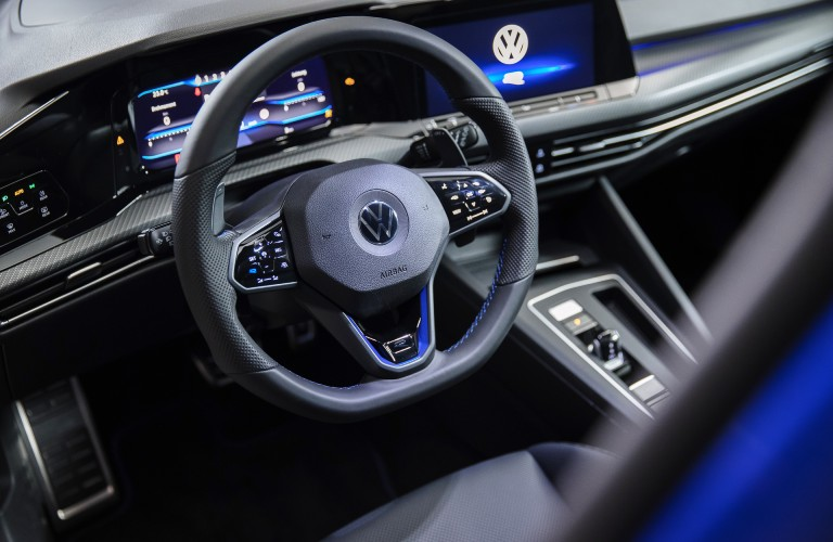 The front interior inside a blue 2022 Volkswagen Golf R.