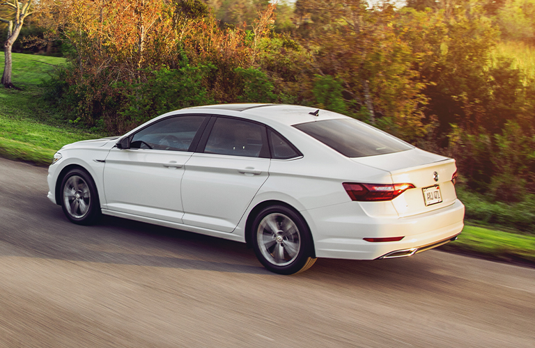 The side and rear view of a white 2021 Volkswagen Jetta.