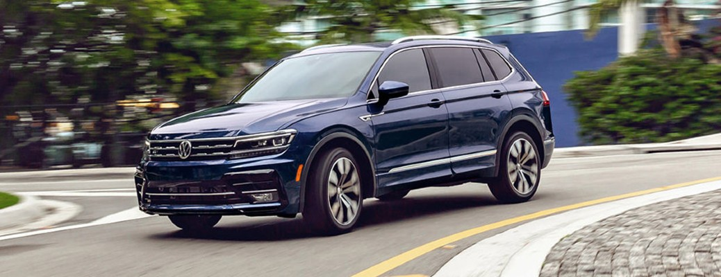 The front and side view of a dark blue 2021 Volkswagen Tiguan.