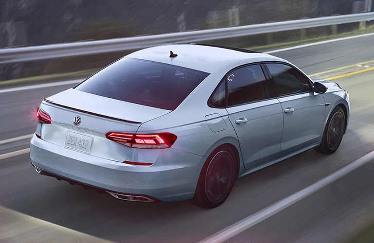 The rear view of a light gray 2021 Volkswagen Passat driving down a road.