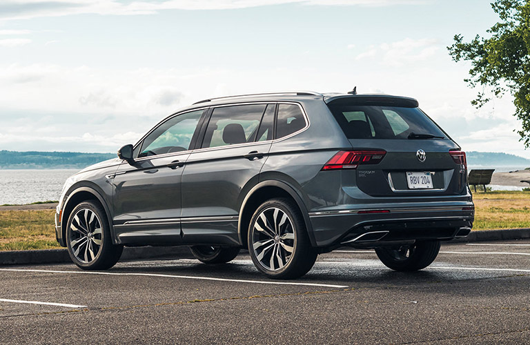 The side and rear view of a gray 2021 Volkswagen Tiguan parked near a lake.