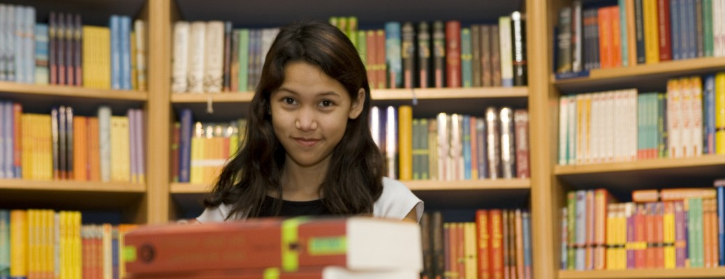 A yount teen girl smirking at the camera in a bookstore.