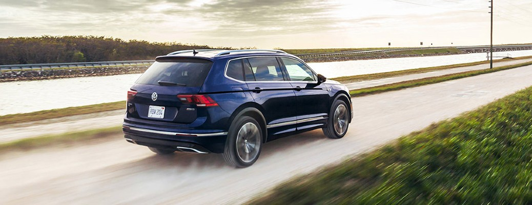 The rear and side view of a blue 2021 Volskwagen Tiguan driving up an empty road.