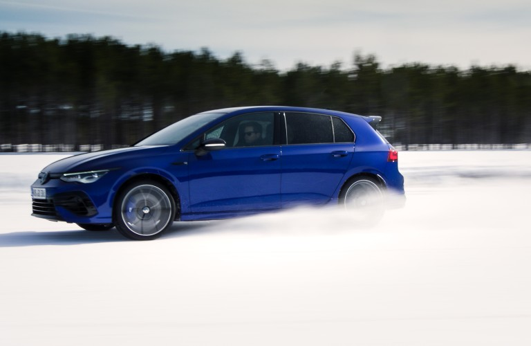 The side view of a blue 2022 Volkswagen Golf R drifting in the snow.