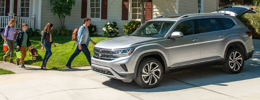 A family walking towards a gray 2021 Volkswagen Atlas.