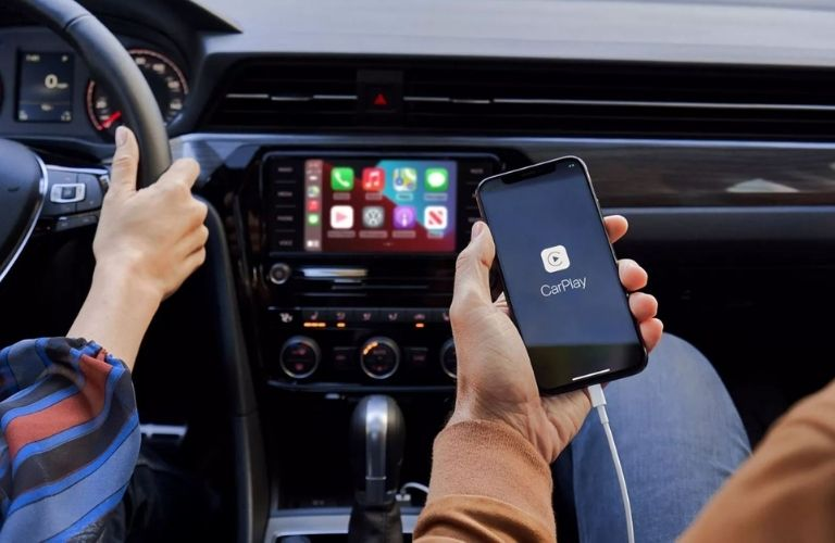 2021 Volkswagen Golf cabin view with a man using a smartphone plugged in to the infotainment system