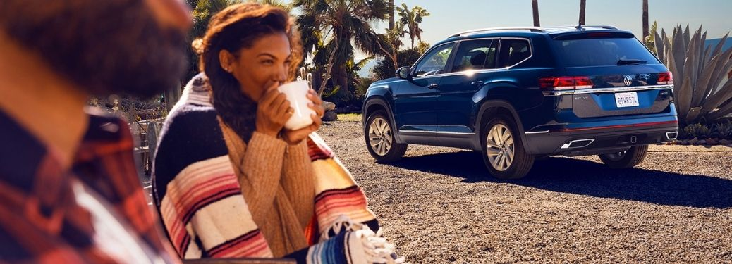 2021 Volkswagen Atlas in the background with a lady in the foreground drinking a cup of coffee
