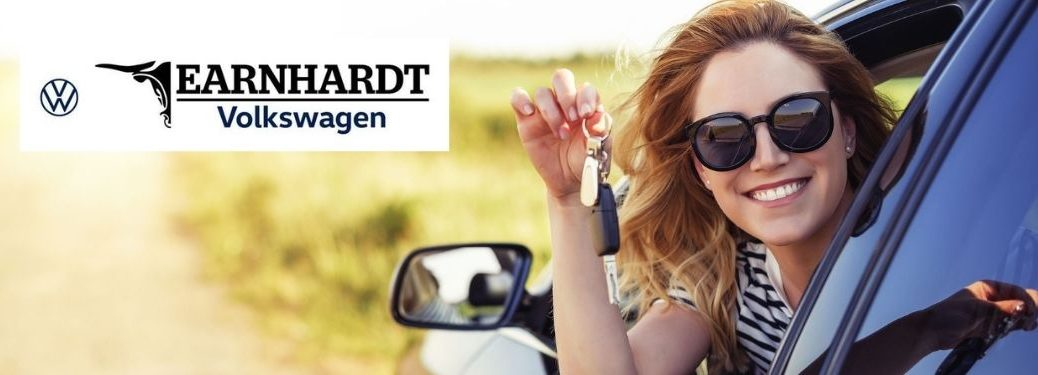 Woman Smiling in New Car with Keys and Earnhardt VW Logo