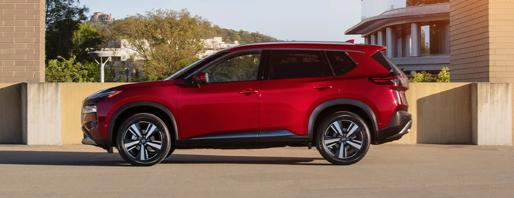 The side view of a red 2021 Nissan Rogue.