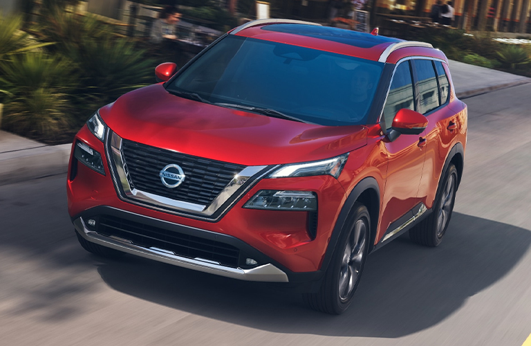 The front side of a red 2021 Nissan Rogue driving down a road.