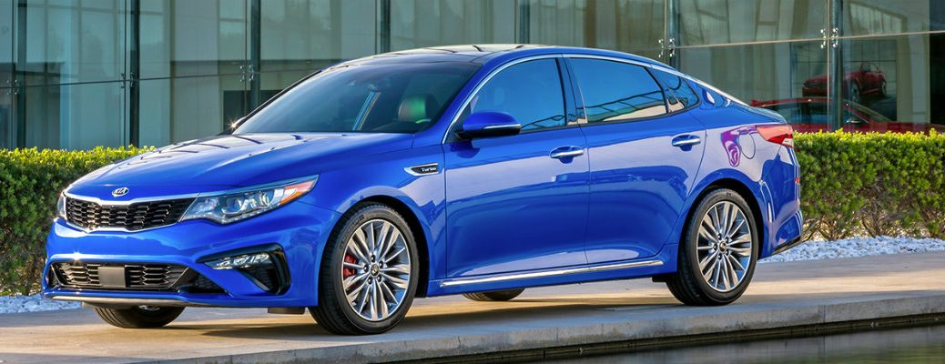 Blue 2019 Kia Optima driving on road in front of modern building