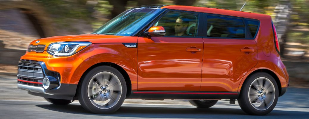 2019 Kia Soul exterior side shot orange paint job driving by a grassy mountainside with a blurry background
