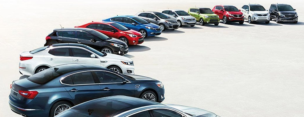A curved line up of Kia models and builds parked on a ligh, sun-bleached stony plateau for Palmen Kia