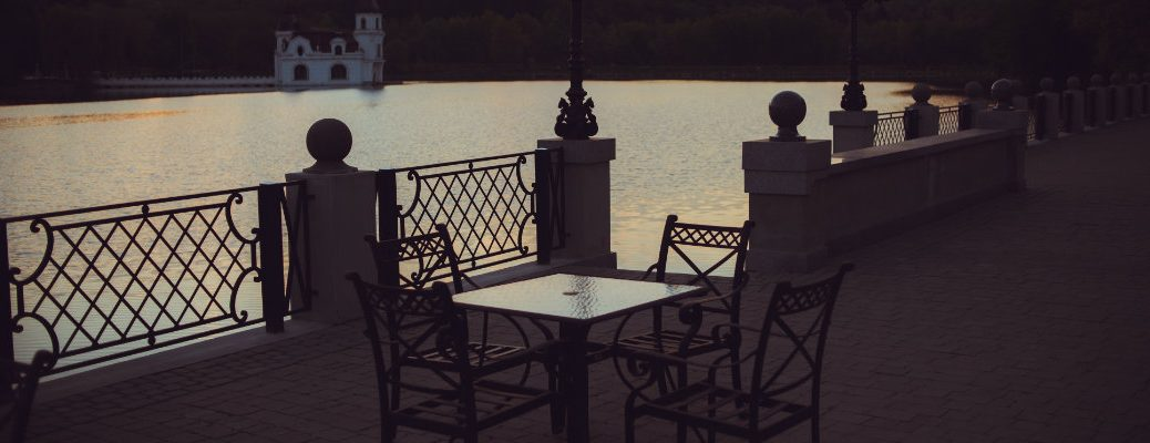 beautfiul terrace patio dining setting cafe by a lake river and castle