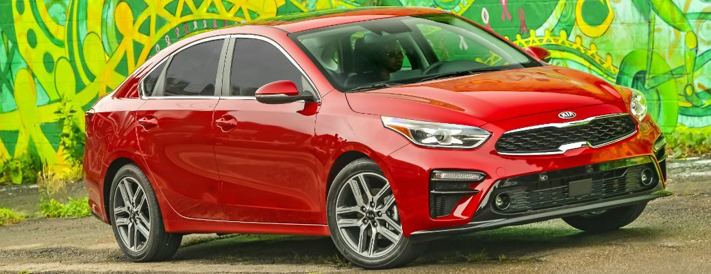 2019 Kia Forte exterior shot redesign with red color paint job parked in front of a wall covered in wild green graffiti