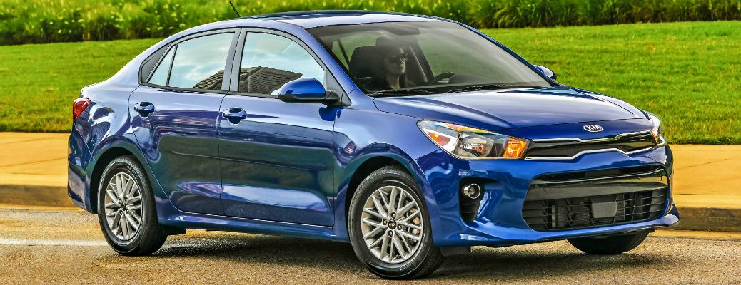 2019 Kia Rio exterior side shot with blue paint color parked near grass and a stone brick wall
