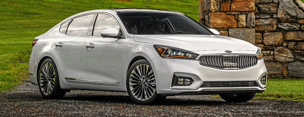 2019 Kia Cadenza luxury sedan with snow white pearl paint color exterior shot parked on a gravel road in the country near a forest and brick wall