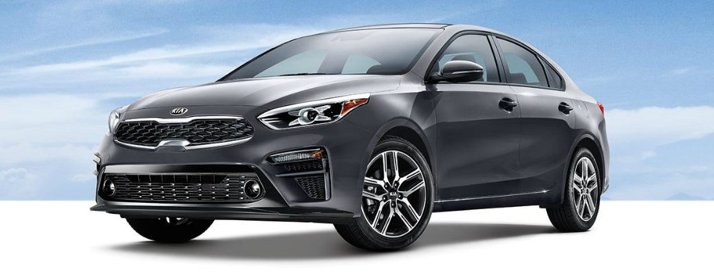 2019 Kia Forte exterior shot with gravity grey paint color parked on a blank white floor under a blue sky of clouds