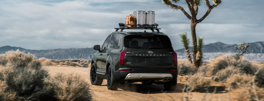 2020 Kia Telluride SUV exterior rear shot with forest green paint color with a load of cargo placed on roof racks while parked in the desert next to a prickly tree