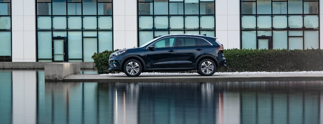 2019 Kia Niro EV exterior side shot parked outside a car dealership as its body reflects off the water