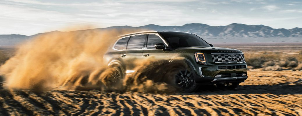2020 Kia Telluride SUV exterior shot with forest green paint color driving through sand dunes and kicking up clouds