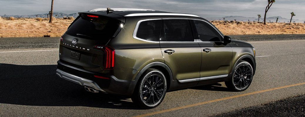 2020 Kia Telluride exterior rear shot with moss green paint color parked on the side of a desert highway