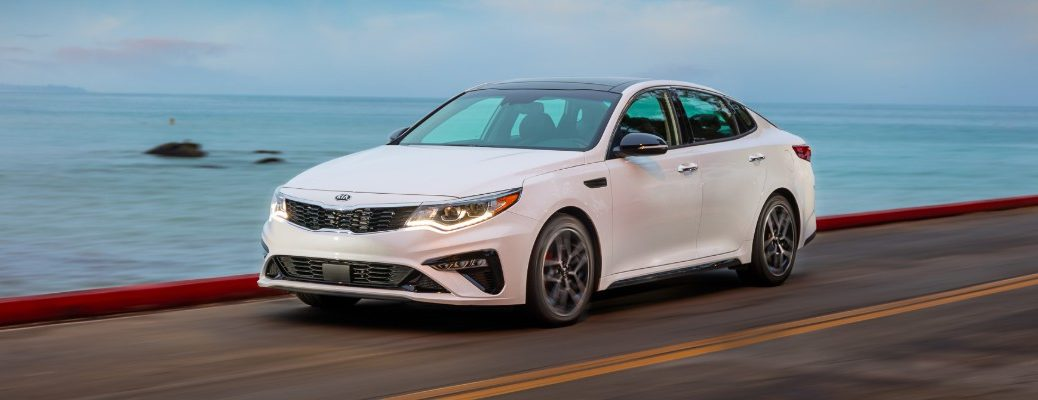 2020 Kia Optima sedan exterior shot with white paint color driving down a highway with LED headlights on near the ocean sea